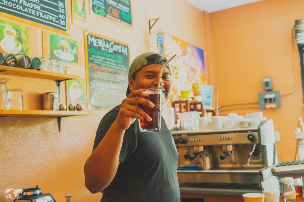 アイスコーヒーを持つ青年プエルトエスコンディードのカフェにて